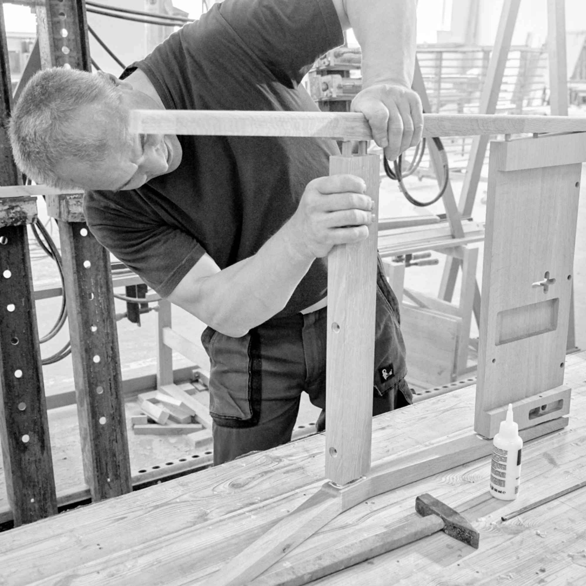 A man pressing oak wood part for production of back of church chair ZOE.
